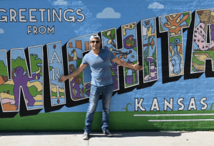 Joey Amato parado frente a un mural que dice Saludos desde Wichita Kansas