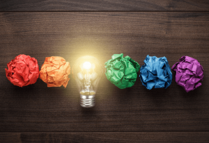 red orange green blue purple crumpled paper with a yellow light bulb in the middle on a brown faux wood background